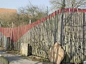 Gartenzaun aus Holz mit roter Farbe dekoriert