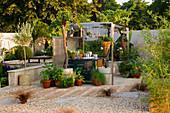 HAMPTON Court FLOWER Show 2006: Designer - PHILIP OSMAN - GRAVEL Garden with OUTDOOR KITCHEN - WOODEN SLEEPER PATH with HERBS IN CONTAINERS. Pergola