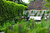 DESIGN: Charlotte ROWE, LONDON. SMALL SECLUDED COUNTRY Garden IN JUNE with Sofa, TRELLIS, Digitalis PURPUREA 'Alba' (White FOXGLOVES) AND PERENNIALS with GLASS LANTERNS