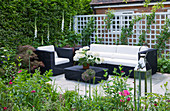 DESIGN: Charlotte ROWE, LONDON.SMALL SECLUDED COUNTRY Garden IN JUNE with Sofa, TRELLIS, Digitalis PURPUREA 'Alba' (White FOXGLOVES) AND OTHER PERENNIALS with GLASS LANTERNS