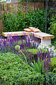Designer: Charlotte ROWE, London: Formal Town / City Garden with WOODEN CORNER BENCH AND CUSHIONS with PLANTING INCLUDING Salvia MAINACHT, PURPURASCENS & CARADONNA. Box CUBES