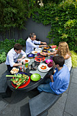 TANIA LAURIE, LONDON. TANIA AND FAMILY SIT DOWN TO LUNCH IN THEIR CONTEMPORARY Garden DESIGNED by Charlotte ROWE