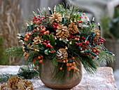 Weihnachtlicher Strauss mit Skimmia (Fruchtskimmie), gebleichten Zapfen