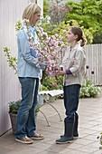 Mädchen gibt Mutter Strauß aus Prunus sargentii 'Accolade'