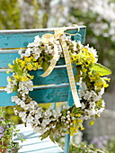Weiß-gelber Frühlingskranz an Stuhllehne