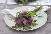 Kleiner Strauß aus Trifolium pratense (Rotklee) und Gräser als Serviettendeko
