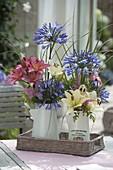 Straeusse in emaillierten Kannen mit Agapanthus (Schmucklilien), Lilium