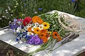 Frau bindet bunten Sommerblumenstrauss