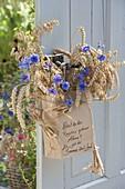 Papiertüte mit Weizen (Triticum), Hafer (Avena) und Centaurea