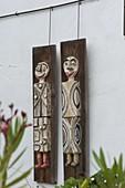 Getoepferte Figuren auf Holzbohlen aufgehängt