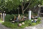Getoepferte Katzen, Kugeln und andere Dekoelemente in Garten
