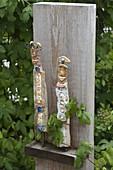 Getoepferte Figuren auf alter Holzbohle