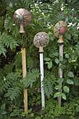 Getoepferte Gartenstecker 'Sonnen' auf Holzstäben im Beet
