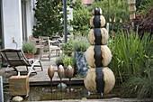 Verschiedene handgetoepferte Wasserspiele im architektonischen Teich