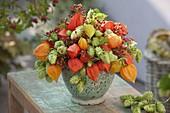 Herbstliches Gesteck aus Physalis (Lampions), Humulus (Hopfen) und Rosa