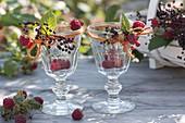 Dekorierte Weingläser mit Himbeeren (Rubus) und Holunder