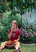 Mädchen sitzt auf der Wiese und nascht Kirschen