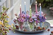 Kerzenglaeser mit Aster (Herbstastern) und Rosa (Hagebutten)
