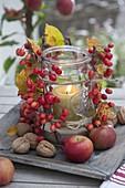 Altes Einmachgglas als Windlicht mit Malus (Zieraepfeln), Kerze und Sand
