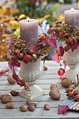Kerzen mit Ranken von Parthenocissus (Wildem Wein) und Rosa