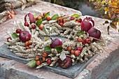 Erntedank-Kranz mit Weizen (Triticum), Äpfeln und Zieraepfeln (Malus)