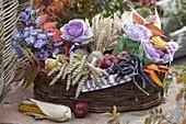 Erntedankkorb mit Weizen (Triticum), Brassica (Zierkohl), schwarzen Bohnen