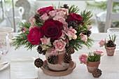 Winterstrauss mit Rosa (Rosen), Zweigen und Zapfen von Pinus (Kiefer)
