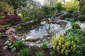 Natürlicher kleiner Teich mit Kies und Natursteinen, Bachlauf im Hintergrund
