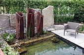 Moderner Teich mit Wasserspiel aus aufgestellten Rohren, Sessel