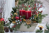 Weihnachtliches Kerzengesteck mit Rosa (gewachster Rose), Zweigen von Ilex