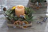 Kerze mit mediterranen Kräutern in Holzschachtel