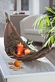 Schale aus Palmblatt mit Kerzen, Orangen (Citrus sinensis