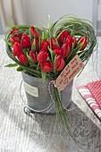Valentinstrauss aus roten Tulpen im Gras-Herz