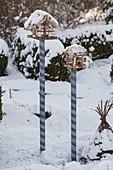 Vogel-Futterhäuschen auf geringelten Holzpfaehlen im verschneiten Garten