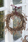 Kranz aus Zweigen von Corylus avellana (Haselnuss) am Fenster