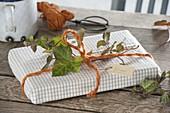 Buch als Geschenk verpackt in Geschirrtuch mit oranger Schnur und Ranke