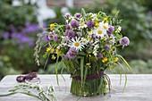 Bunter Wiesenstrauss in mit Gras verkleideter Vase