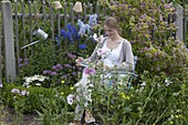 Junge Frau sitzt im Bauerngarten zwischen Blumen und liest