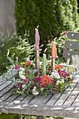 Kranz aus Lathyrus odoratus (Duftwicken) und Zinnien um Kerzenhalter auf Table