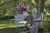 Gedeckter Tisch unterm Apfelbaum mit Strauss aus Sommerblumen