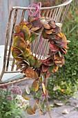 Kränzchen aus Blättern von Amelanchier (Felsenbirne) an Stuhllehne