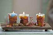 Kleine Windlichter mit Blättern umwickelt, Rosa (Hagebutten) und Walnuessen