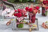 Rot-weisse Trinkbecher als Vasen mit Bergenien-Blättern