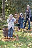 Laub rechen mit Kindern und Hund