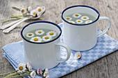Tee mit Gänseblümchen (Bellis perennis) in Emaille-Bechern