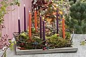 Kranz aus Naturmaterialien mit Kerzen auf Holz-Tablett