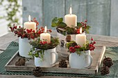 Ungewoehnlicher Adventskranz in Emaille-Bechern , dekoriert mit Ilex