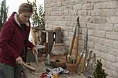 Frau säubert Spaten mit einer Bürste, saubere Werkzeuge lehnen
