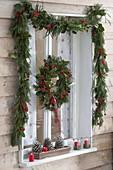 Fenster mit Girlande und Kranz weihnachtlich schmücken