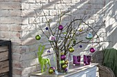 Weihnachtlicher Strauss aus trockenen Ästen mit Baumschmuck